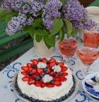 härlig gräddtårta med skivade jordgubbar och blåbär under bukett av syrener på dukat sommarbord.