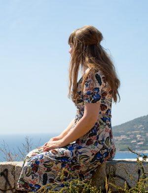 Clara fotad bakifrån sitter och tittar ut över havet