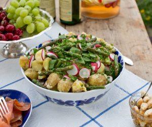 Dukat sommarbord med stora skålar fyllda med bland annat potatisallad, vindruvor och grönsaker.