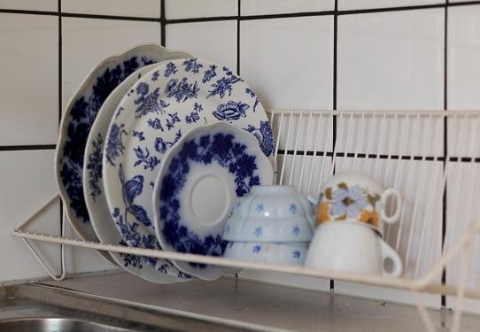 Blått porslin i udda mönster i diskställ.
