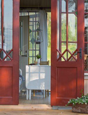 Punchveranda med öppna dörrar i grönska.