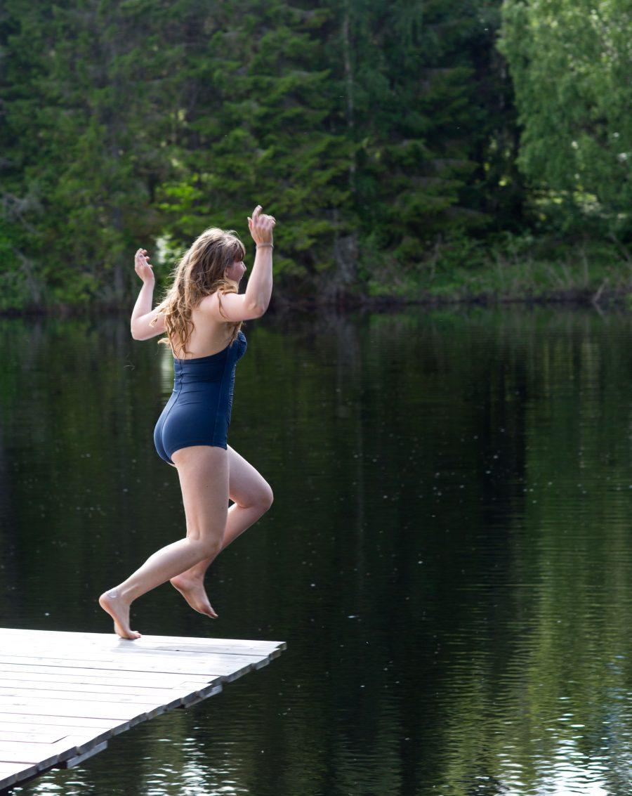 Clara hoppar från badbrygga mot klart vatten med skog i bakgrunden.