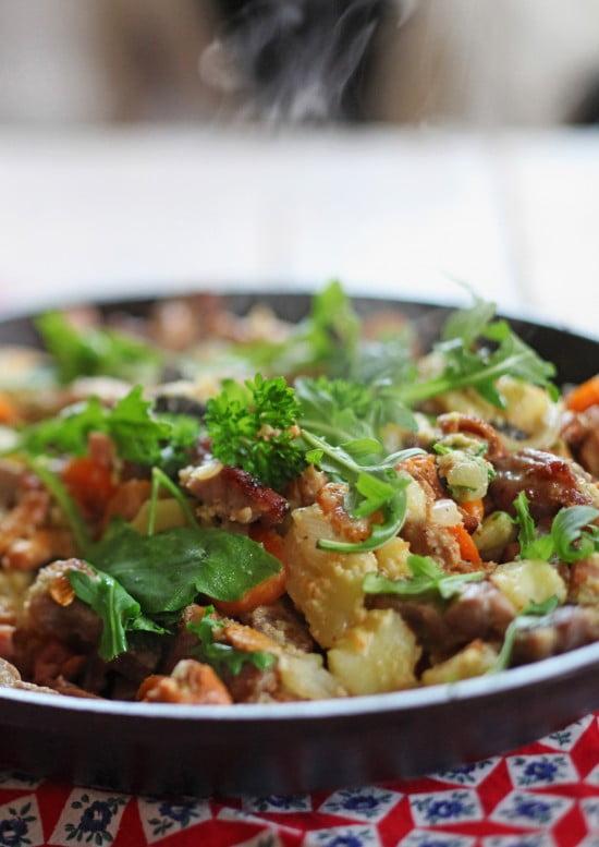 Panna med älgkött, rykande kantareller och gröna blad på toppen.