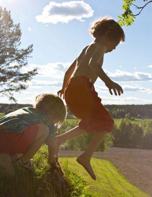 Pojkarna Bertil och Folke hoppar från en sten utomhus i sommarväder.
