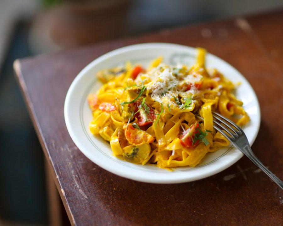 Gul pasta färgad av saffran ligger på en enkel tallrik, i pastan skymtar grönsaker som små tomater.