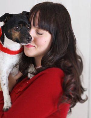 Clara i mörkt långt hår och röd kofta kramar hunden Melker som har en röd rosett om halsen.
