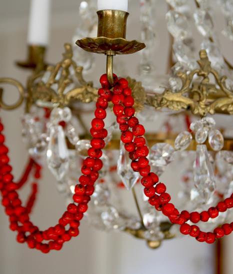 Girland av rönnbär trädda på tråd som hänger som dekoration i en kristallkrona.