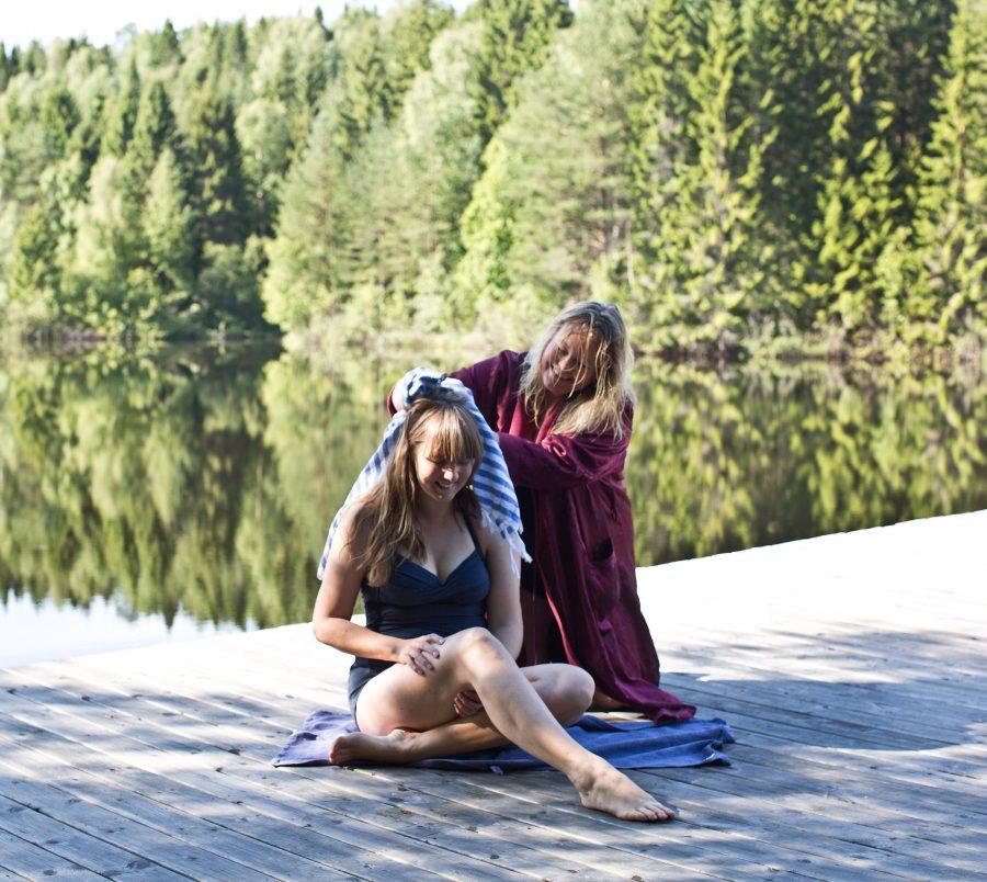 Clara och Erica i badkläder på en brygga vid badsjö, Erica tokar klara i håret med en handduk. Ur En Underbar Pod.