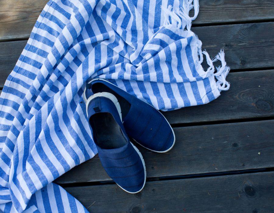 Blå sommarskor och en randig handuk på träbrygga.