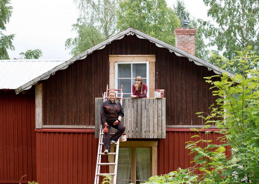 Erica och Clara framför ett halvmålat fritidshus. Clara står på husgavelns balkong och Erica på en stege upp mot balkongen i målarkläder. Från En Underbar Pod.