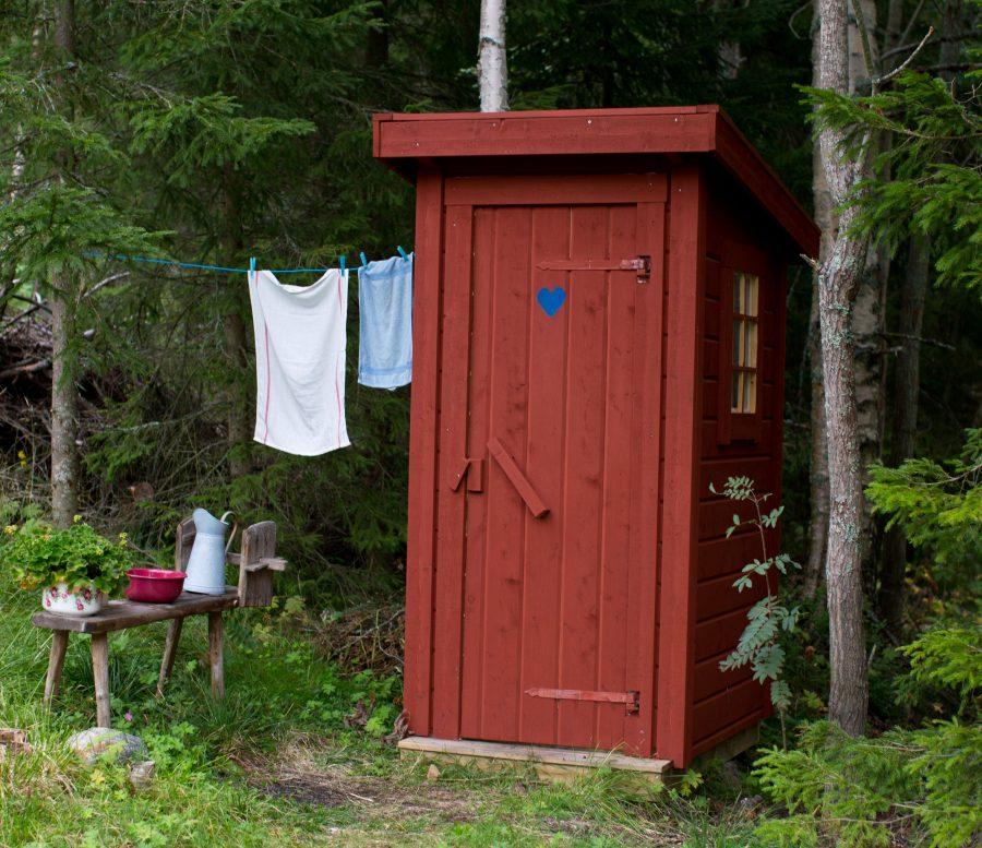 Rött litet utedass med blått hjärta på dörren, Intill står en träbänk med vattenkanna i plåt och ett tvättfat. Ovanför hänger kort klädsträck med handdukar att torka sig på. Från En Underbar Pod, Ericas fritidshus.