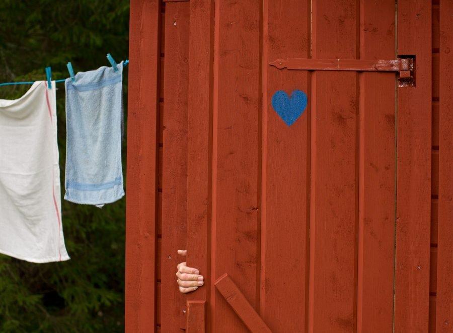 Fingrar som håller i en dassdörr från insidan, en person är på väg in på utedasset för att låsa om sig. Ur En Underbar Pod, från Ericas fritidshus.