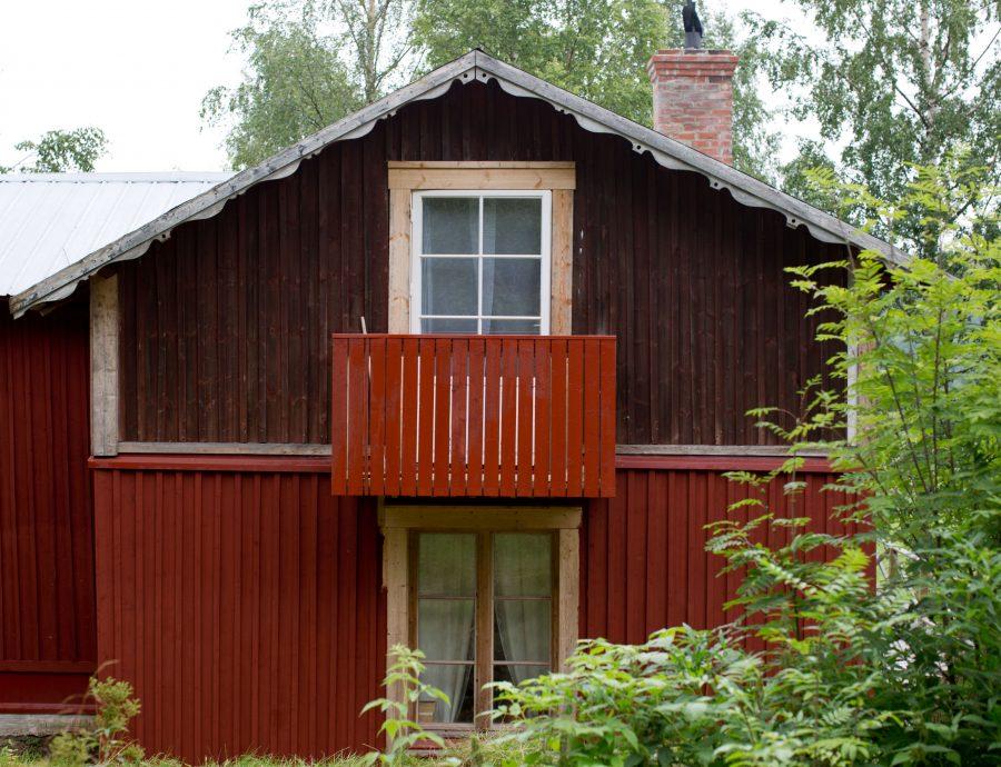 Gavelvägg på gammalt rött trähus. Halva väggen är målad och balkongen i falu rött. Från En Underbar Pod, Ericas fritidshus.