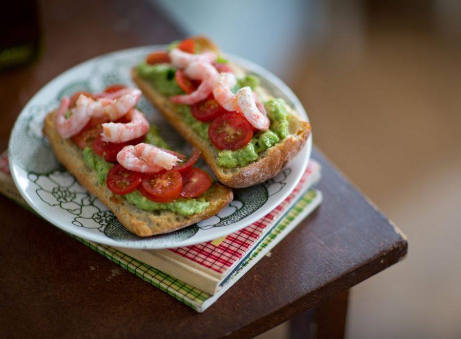 Lunchsmörgås i två delar med skaldjur, avokadoröra och tomat på. Ligger på tallrik som står på en träpall.