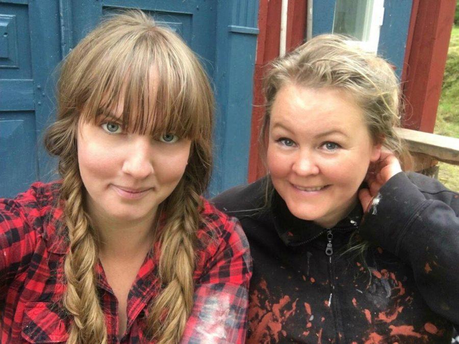 Clara och Erica i färgfläckiga målarklädar, Clara i flätor och Erica med hår uppsatt för arbete. Ur En Underbar Pod, från Ericas fritidshus.