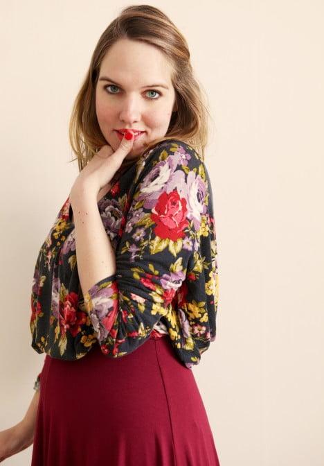 Clara i blommig blus och vinröd långkjol tittar in i kameran med försiktigt leende.