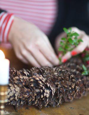 Kottkrans där händer binder fast små kvistar med röda lingon i. Ur En Underbar Pod.