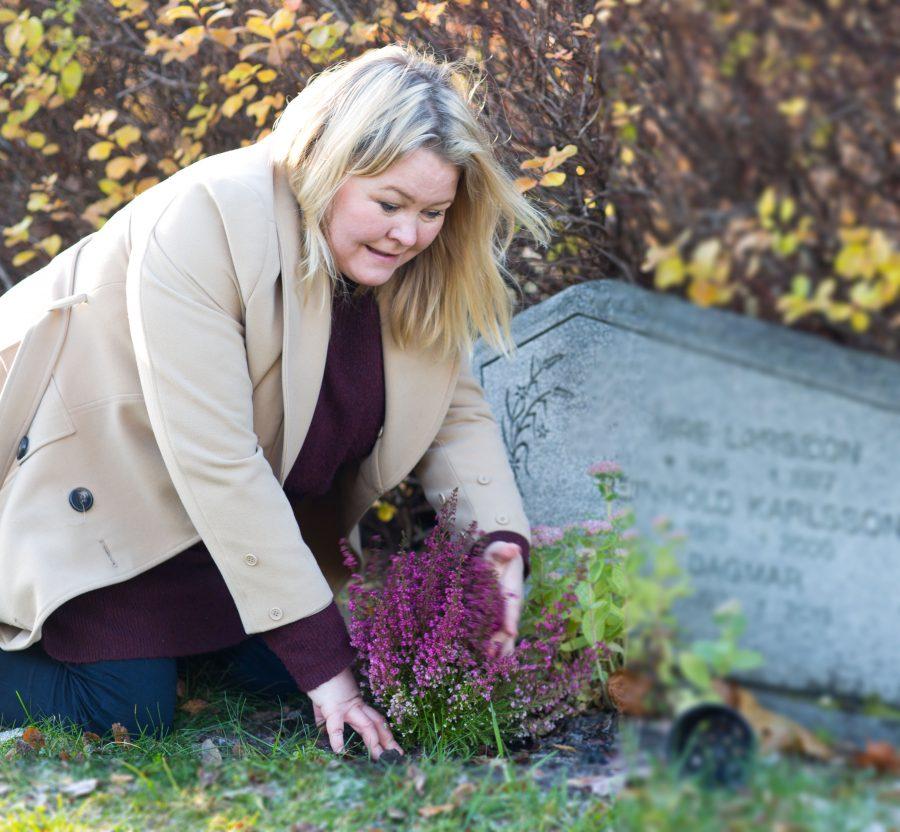 Erica planterar en ljug på sin morfars grav på Backens kyrkogård i Umeå. Ur En Underbar Pod.