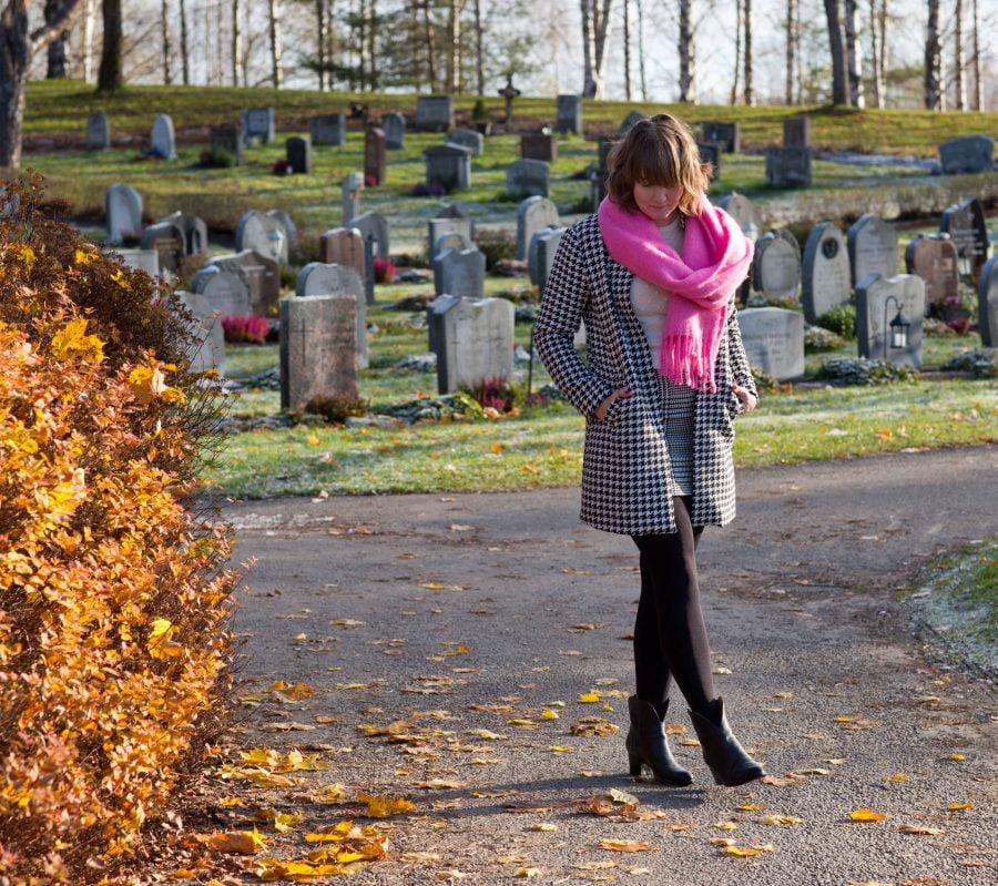 Clara höstklädd i rosa halsduk på Backens kyrkogård i Umeå. Ur En Underbar Pod.