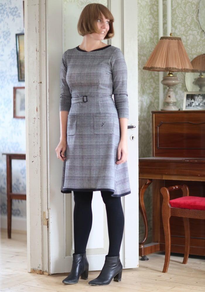 Clara i page och svartvit klänning med rutmönster ler men tittar inte in i kameran.