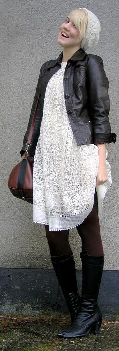 Clara i vit spetsliknande klänning och mörk skinnjacka och svarta stövlar med klack.