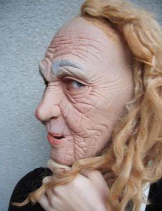 Ansiktsmask föreställande rynkig gammal häxa eller trollgubbe med långt hår som tittar in mot kameran.