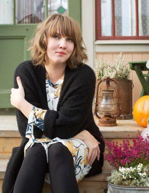Clara på trappan utanför sitt hus i höstkofta. På trappstegen står en pumpa, lyktor och höstblommor.