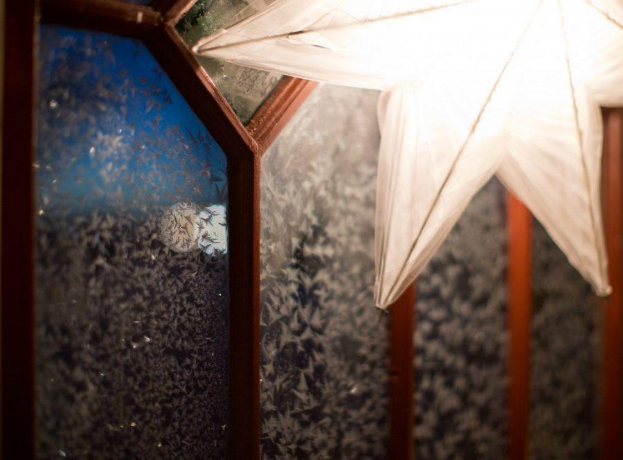 Vit julstjärna med kallt ljus skiner mot glasruta fyllt med froststjärnor i glaset.