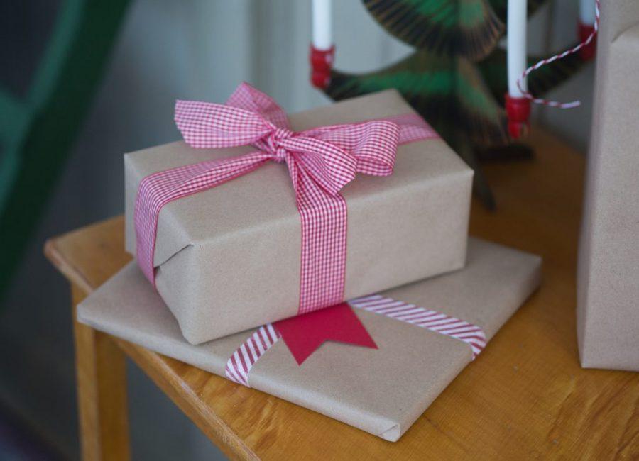 Vackert inslagna julpaket, julklappar i rött och vitt och brunt papper.