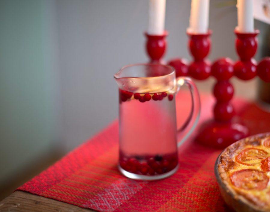 Julbord med röd ljusstake och kanna i glas.