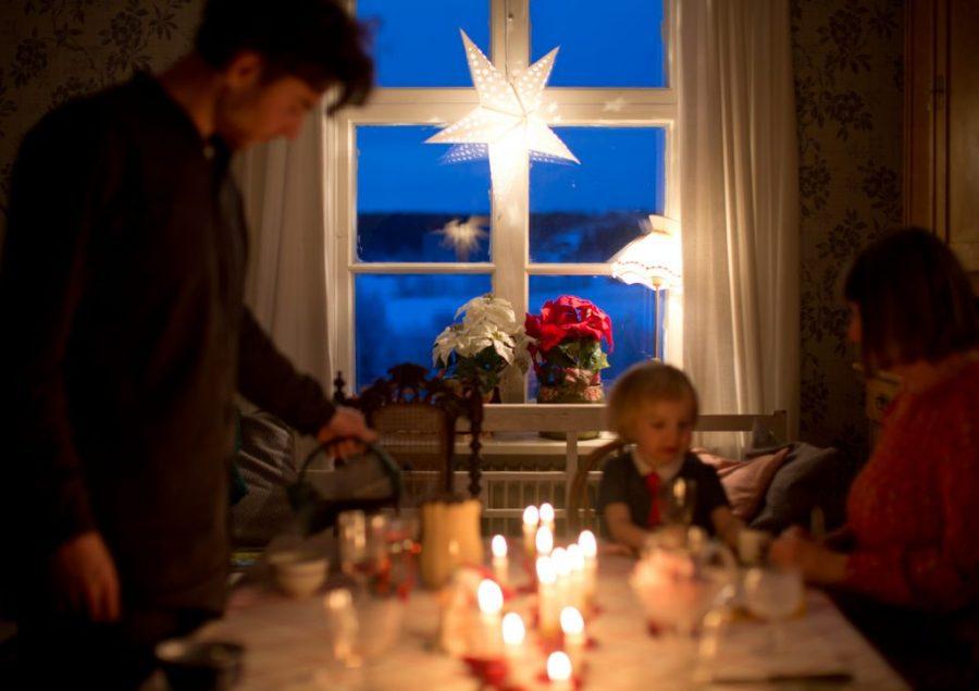 Hela familjen samlade runt matbordet i med levande ljus i mörk vinterkväll. Adventsstjärna i fönstret.