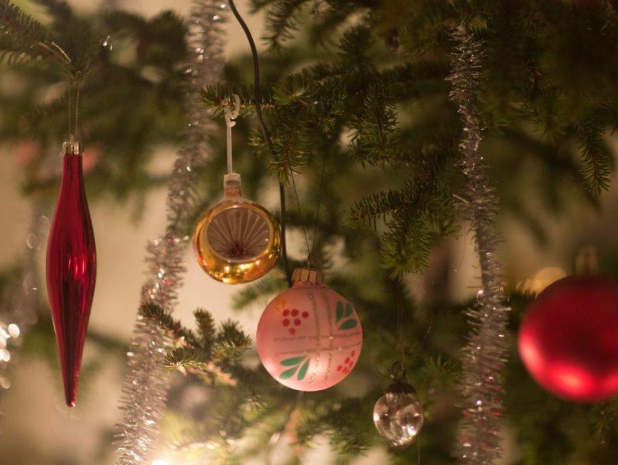 Närbild på julgransgren fylld av julkulor och glansiga pumlor