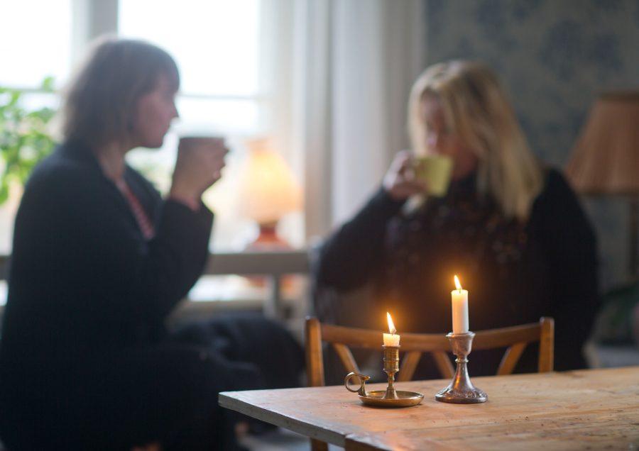 Clara och Erica dricker te hemma hos Clara. På bordet står levande ljus. Ur En Underbar Pod.