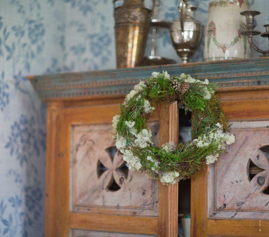 Krans av vit och grön mossa och mörka kvistar som hänger mot gammaldags skåpdörr. Ur En Underbar Pod.
