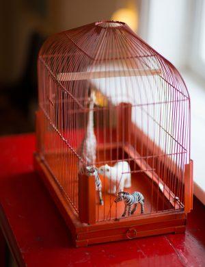 Gammeldags fågelbur med leksaksdjur arrangerade som ett öppet zoo.