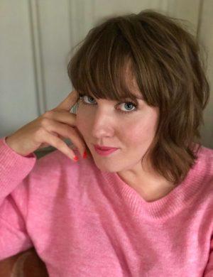 Clara i rosa stickad tröja tittar in i kameran och ler.