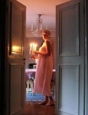 Clara i vitt långt nattlinne, bär en kandelaber med levande ljus genom ett mörkt rum.
