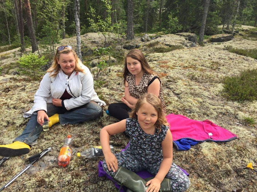Erica med sina döttrar Isa och Maria på en utflykt, de sitter på ett berg och fikar. Ur En Underbar Pod.