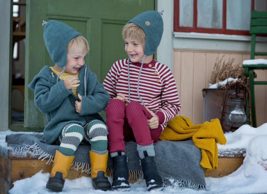 Folke och Bertil på snöig utetrappa. Tittar på varandra och skrattar.
