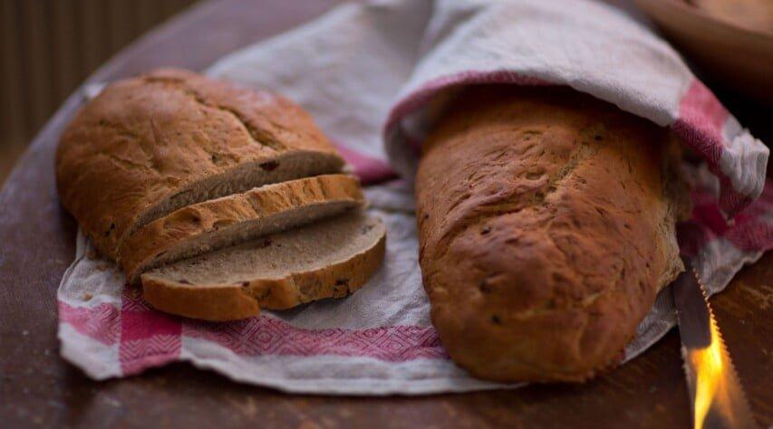 Brödlimpor i kökshandduk, en av limporna har börjat skäras upp i tunna skivor.
