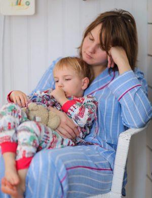 Clara med sonen Folke i knät sitter och halvsover i en korgstol, klädd i pyjamas