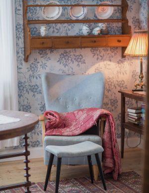Blå gammaldags fåtölj står i vardagsrum under tallrikshylla.