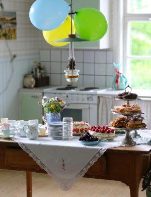 Köksbord i trä med kalasdukning med många sorters godsaker och ballonger som hänger ner från kökslampan