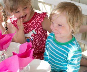 Festdukat bord med färgglada servetter som står upp i glasen. Claras son Folke med kusinen Juni intill som tittar på honom.