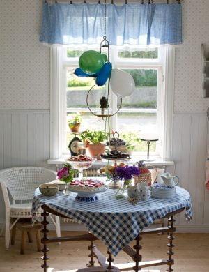 Dukat för sommarkalas med ballonger och godsaker på träbord i lantkök.