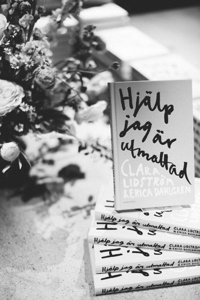 Boken Hjälp jag är utmattad i svartvitt med blommor intill.