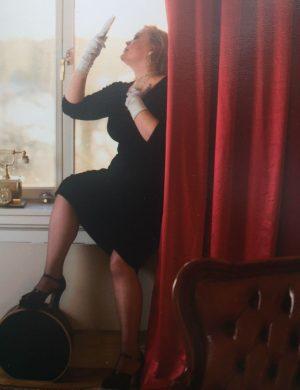 Erica sitter i fönster i mörk sammetsklänning så valkar syns i midjan. Ur En Underbar Pod. Tjica.