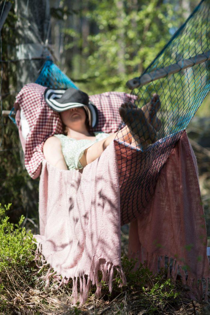 Clara ligger och vilar under solhatt i en hängmatta. Från En Underbar Pod.