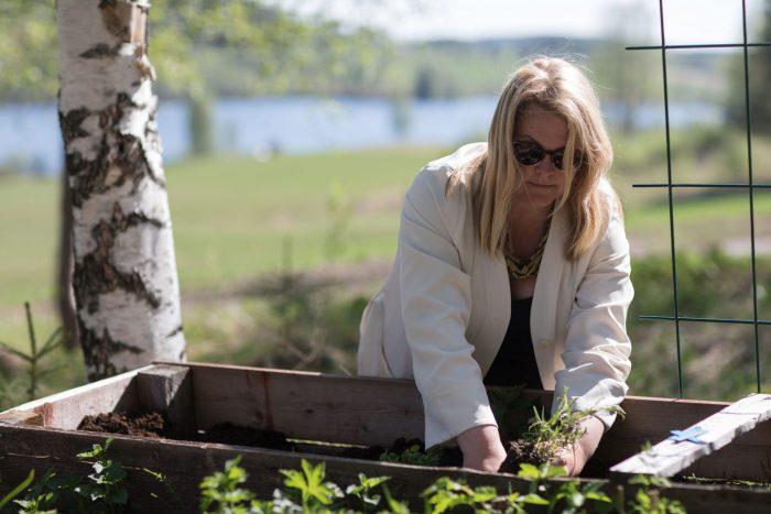 Erica planterar blommor i låda iklädd ljus kappa och solglasögon. Ur En Underbar Pod.