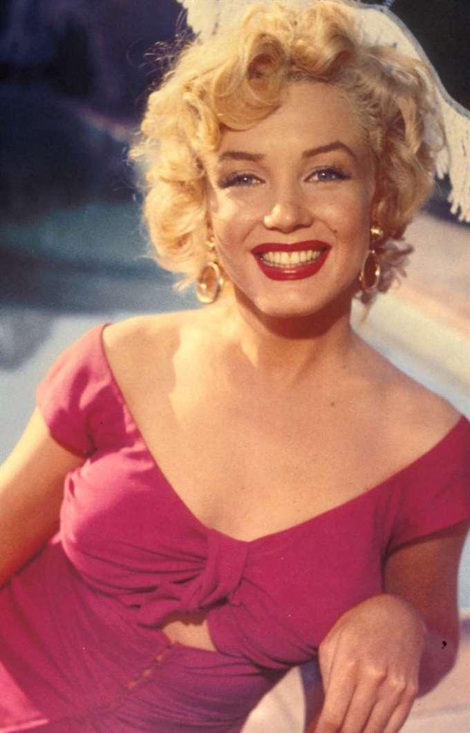 Marilyn Monroe ler mot kameran i röd klänning.